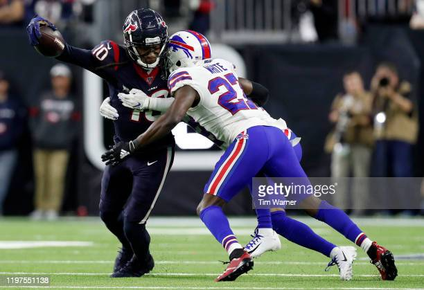 Wide receiver DeAndre Hopkins of the Houston Texans fumbles on a hit by Micah Hyde of the Buffalo Bills during the AFC Wild Card Playoff game at NRG...