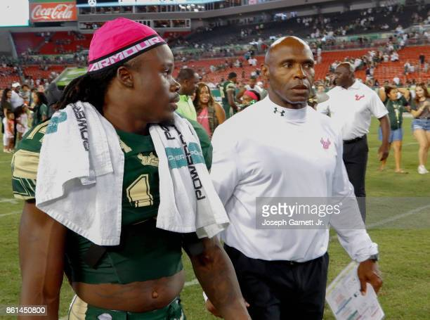 Wide receiver Deangelo Antoine of the South Florida Bulls walk across the field with head coach Charlie Strong after defeating Cincinnati Bearcats...