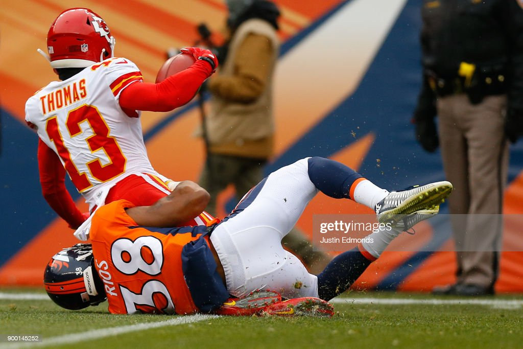 Wide receiver De'Anthony Thomas #13 of the Kansas City Chiefs rolls his ankle while being tackled by cornerback Marcus Rios #38 of the Denver Broncos during the first quarter at Sports Authority Field at Mile High on December 31, 2017 in Denver, Colorado.