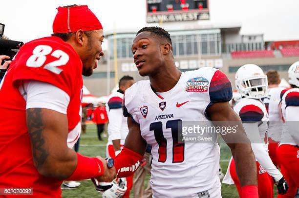 Wide receiver Delane HartJohnson of the New Mexico Lobos congratulates safety Will Parks of the Arizona Wildcats at University Stadium on December 19...
