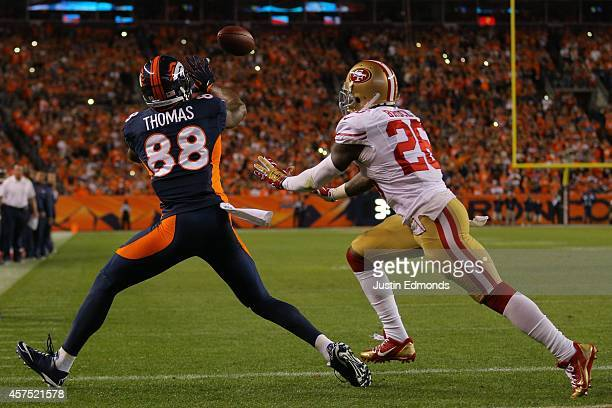 Wide receiver Demaryius Thomas of the Denver Broncos catches a touchdown pass from Peyton Manning under coverage by cornerback Tramaine Brock of the...