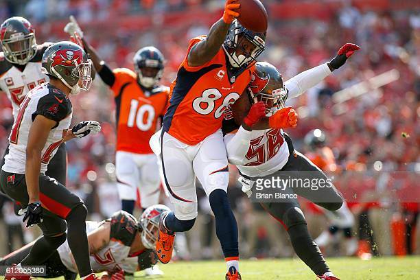 Wide receiver Demaryius Thomas of the Denver Broncos fends off middle linebacker Kwon Alexander of the Tampa Bay Buccaneers as crosses the goal line...