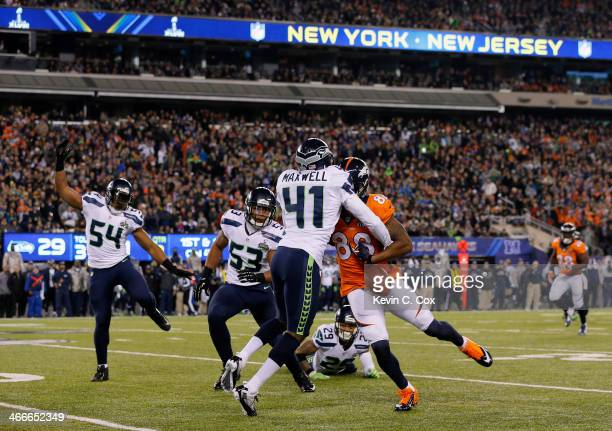 Wide receiver Demaryius Thomas of the Denver Broncos goes up to catch a ball he fumbles against middle linebacker Bobby Wagner of the Seattle...