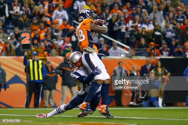 Wide receiver Demaryius Thomas of the Denver Broncos is hit by cornerback Stephon Gilmore of the New England Patriots as Thomas scores a third...
