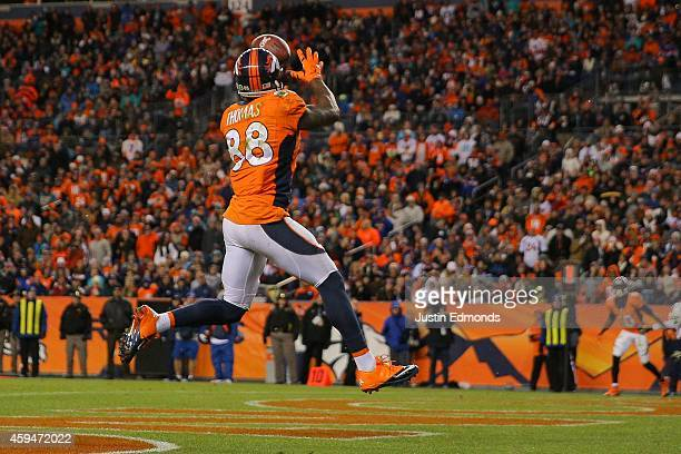 Wide receiver Demaryius Thomas of the Denver Broncos leaps to catch a 5-yard pass mid-stride in the end zone for a third quarter touchdown, his third...