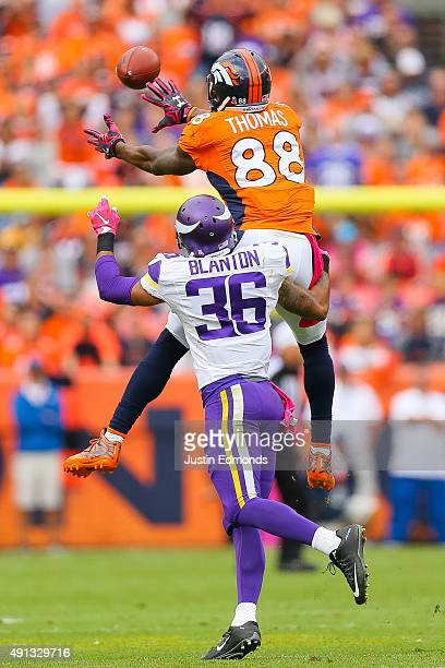 Wide receiver Demaryius Thomas of the Denver Broncos leaps to make a catch under coverage by strong safety Robert Blanton of the Minnesota Vikings...