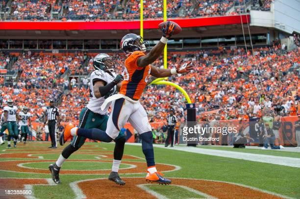 Wide receiver Demaryius Thomas of the Denver Broncos scores a third quarter touchdown under coverage by cornerback Bradley Fletcher of the...