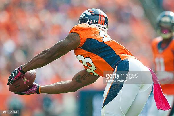 Wide receiver Demaryius Thomas of the Denver Broncos wearing pink gloves and a pink towel catches a ball adorned with a pink ribbon to promote breast...