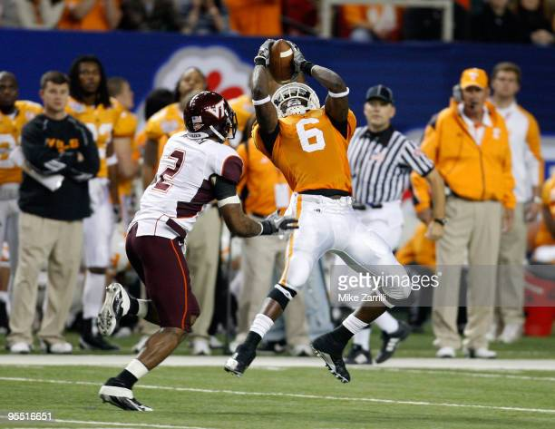 Wide receiver Denarius Moore of the Tennessee Volunteers hauls in a second quarter pass while defensive back Devon Morgan of the Virginia Tech Hokies...