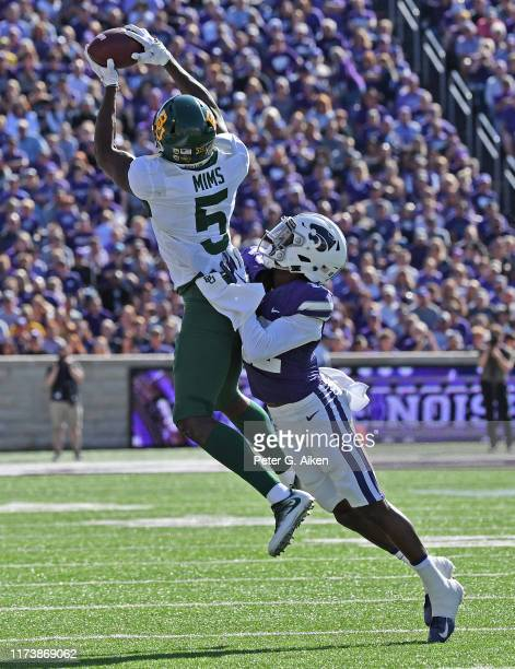 Wide receiver Denzel Mims of the Baylor Bears catches a pass against defensive back AJ Parker of the Kansas State Wildcats during the first half at...