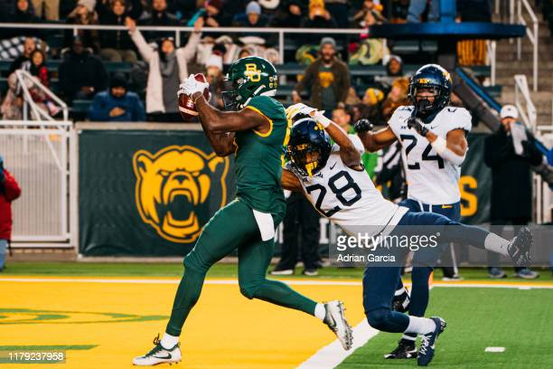 Wide receiver Denzel Mims of the Baylor Bearson runs past cornerback Keith Washington Jr #28 of the West Virginia Mountaineers and cornerback Hakeem...