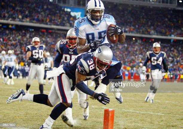 Wide receiver Derrick Mason of the Tennessee Titans leaps over defensive back Tyrone Poole of the New England Patriots to score a touchdown in the...