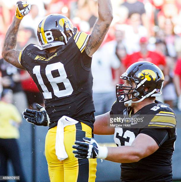 Wide receiver Derrick Willies celebrates with offensive lineman Austin Blythe of the Iowa Hawkeyes after scoring a touchdown in the fourth quarter...