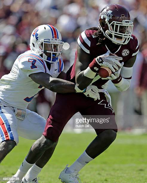 Wide receiver De'Runnya Wilson of the Mississippi State Bulldogs catches a pass as he is tackled by safety Xavier Woods of the Louisiana Tech...