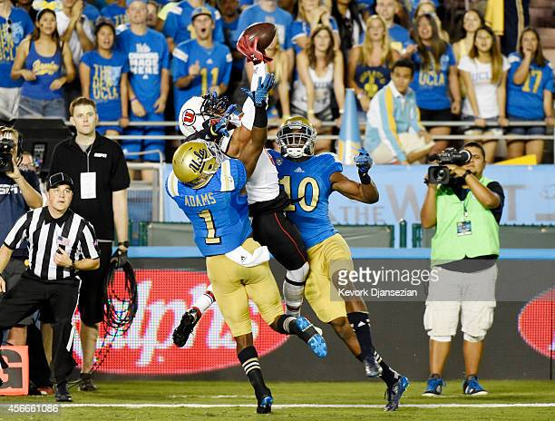 Wide receiver Des Anderson of the Utah Utes catches a pass and scores a touchdown against Ishmael Adams and Fabian Moreau of the UCLA Bruins during...