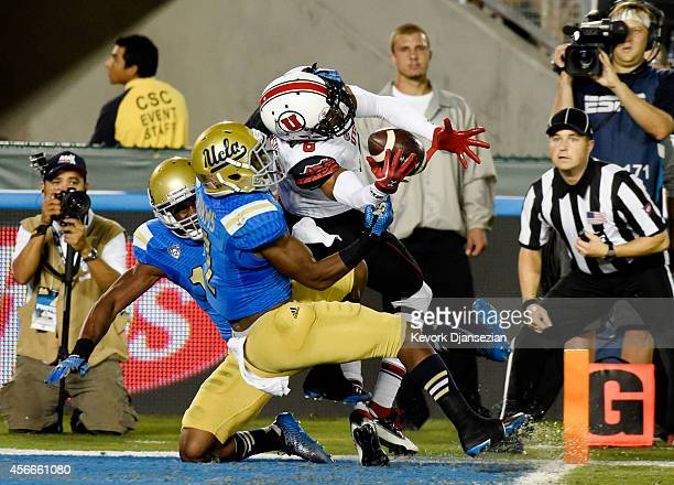 Wide receiver Des Anderson of the Utah Utes hangs on to the ball as he score s touchdown against Ishmael Adams and Fabian Moreau of the UCLA Bruins...