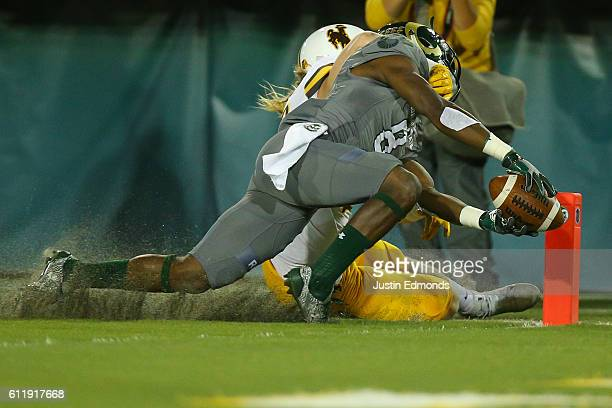 Wide receiver Detrich Clark of the Colorado State Rams reaches the ball across the goal line for a touchdown before being tackled by safety Andrew...