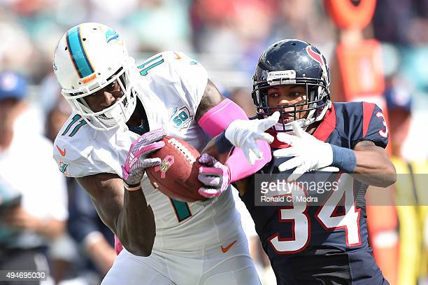 Wide receiver DeVante Parker of the Miami Dolphins catches a pass as AJ Bouye of the Houston Texans defends during a NFL game against the Miami...