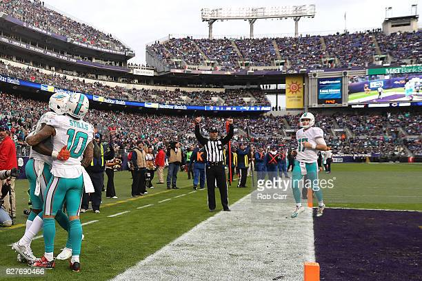 Wide receiver DeVante Parker of the Miami Dolphins celebrates with teammate wide receiver Kenny Stills and quarterback Ryan Tannehill after scoring a...