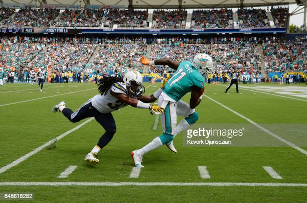 Wide receiver DeVante Parker of the Miami Dolphins slips past free safety Tre Boston of the Los Angeles Chargers as he makes a catch and runs for big...