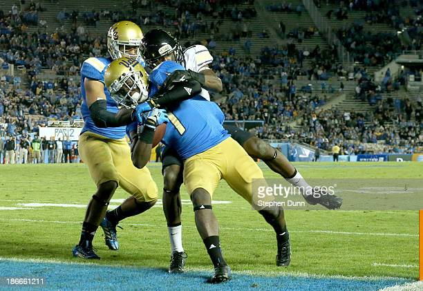 Wide receiver Devin Fuller of the UCLA Bruins crosses the goal line as cornerback Jeffrey Hall of the Colorado Buffaloes tries to make the tackle on...