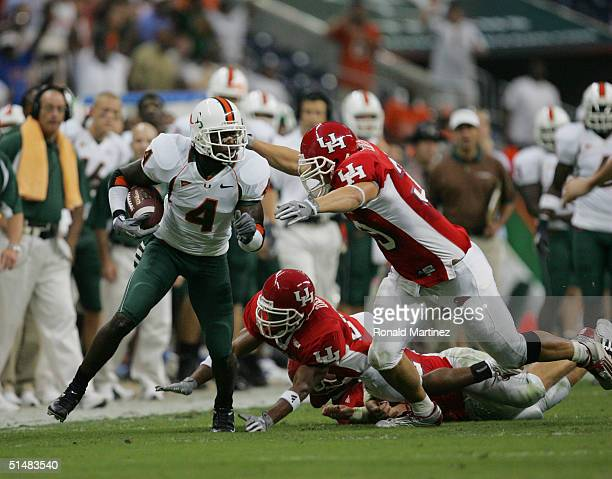 Wide receiver Devin Hester of the University of Miami Hurricanes carries the ball while evading tackles during the game with the University of...