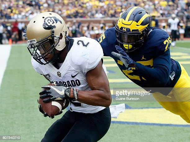 Wide receiver Devin Ross of the Colorado Buffaloes catches a touchdown pass in front of safety Dymonte Thomas of the Michigan Wolverines during the...