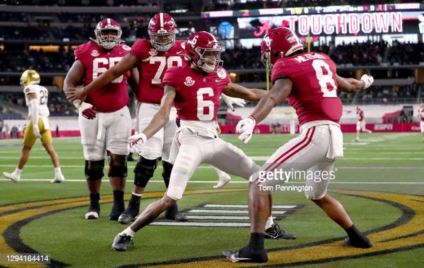 Wide receiver DeVonta Smith of the Alabama Crimson Tide celebrates his touchdown with teammate wide receiver John Metchie III in the first quarter of...