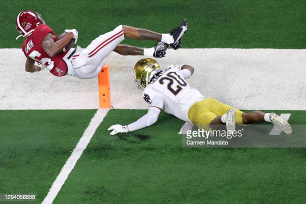Wide receiver DeVonta Smith of the Alabama Crimson Tide dives over safety Shaun Crawford of the Notre Dame Fighting Irish for a touchdown in the...