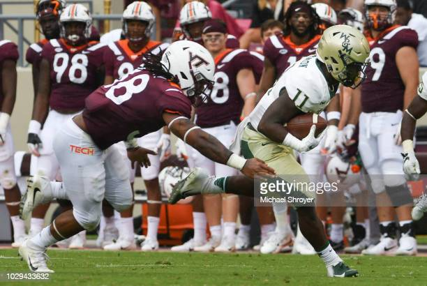 Wide receiver DeVonte Dedmon of the William Mary Tribe carries the ball following his reception while being pursued by linebacker Rico Kearney of the...