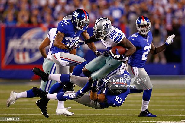 wide receiver Dez Bryant of the Dallas Cowboys gets tackled by linebacker Chase Blackburn and defensive back Michael Coe of the New York Giants...