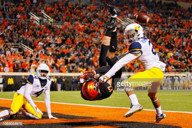 Wide receiver Dillon Stoner of the Oklahoma State Cowboys gets upside down in the end zone as the ball come loose over the head of safety Kenny...