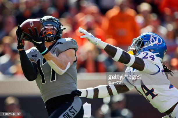 Wide receiver Dillon Stoner of the Oklahoma State Cowboys pulls down a catch for a 51yard touchdown against safety Ricky Thomas of the Kansas...