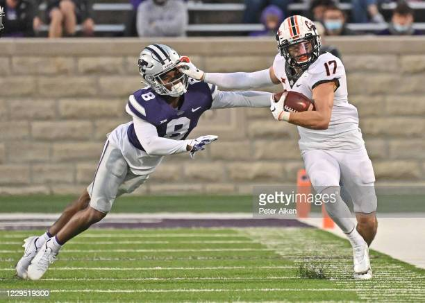 Wide receiver Dillon Stoner of the Oklahoma State Cowboys puts a stiff-arm on defensive back Tee Denson of the Kansas State Wildcats, after catching...