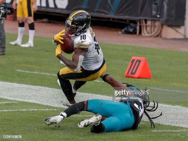 Wide receiver Diontae Johnson of the Pittsburgh Steelers makes a catch over cornerback Tre Herndon of the Jacksonville Jaguars during the game at...