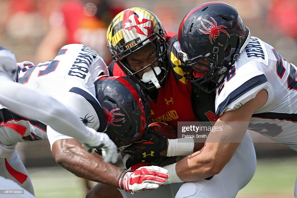 Wide receiver D.J. Moore #1 of the Maryland Terrapins is tackled by defensive back David Herlocker #28 and linebacker Omar Howard #46 of the Richmond Spiders in the first quarter at Byrd Stadium on September 5, 2015 in College Park, Maryland.