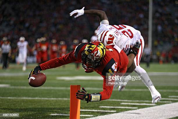 Wide receiver D.J. Moore of the Maryland Terrapins scores touchdown in front of cornerback Derrick Tindal of the Wisconsin Badgers during the second...