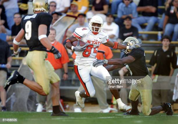 Wide receiver D'Juan Woods of the Oklahoma State Cowboys cuts his way to a 53-yard touchdown through the arms of Tyrone Henderson of the Colorado...