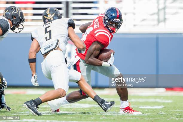 Wide receiver DK Metcalf of the Mississippi Rebels looks to maneuver the ball by safety LaDarius Wiley of the Vanderbilt Commodores at...