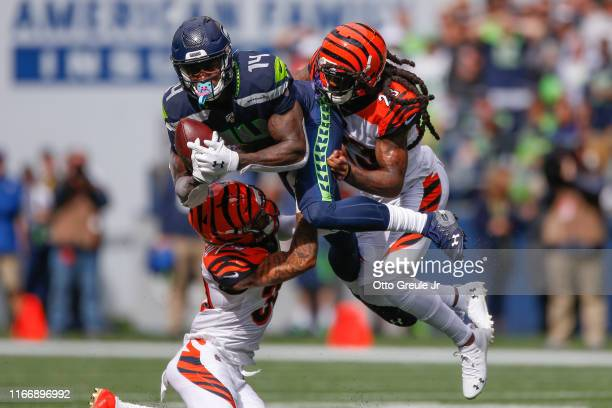Wide receiver DK Metcalf of the Seattle Seahawks makes a catch against safety Jessie Bates and cornerback BW Webb of the Cincinnati Bengals in the...