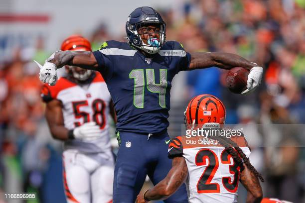 Wide receiver DK Metcalf of the Seattle Seahawks reacts after making a catch against safety Jessie Bates and cornerback BW Webb of the Cincinnati...