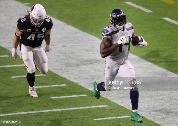 Wide receiver DK Metcalf of the Seattle Seahawks runs with the football after a reception ahead of linebacker Dennis Gardeck of the Arizona Cardinals...