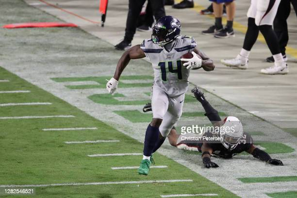Wide receiver DK Metcalf of the Seattle Seahawks runs with the football after a reception ahead of strong safety Budda Baker of the Arizona Cardinals...