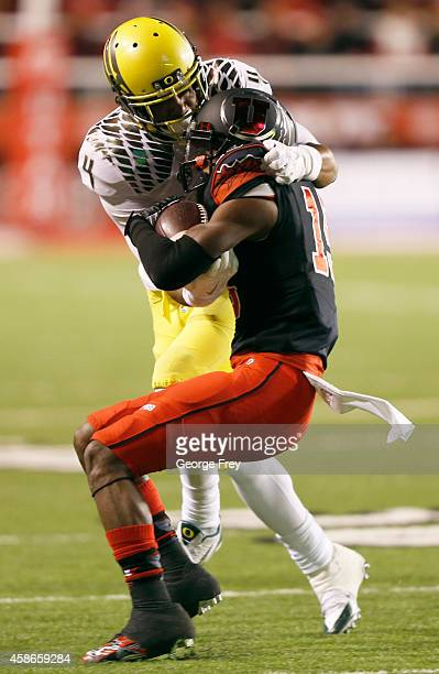 Wide receiver Dominique Hatfield of the Utah Utes is stopped short of a first down on a fourth down by defensive back Erick Dargan of the Oregon...