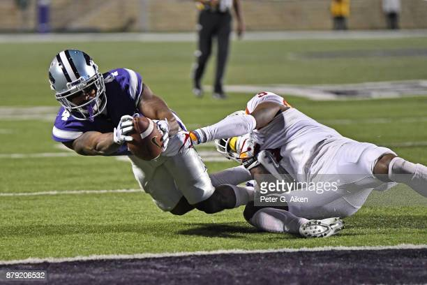Wide receiver Dominique Heath of the Kansas State Wildcats reaches the ball out to the one yard line against strong safety Reggie Wilkerson of the...