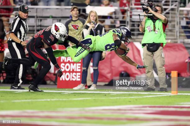 Wide receiver Doug Baldwin of the Seattle Seahawks dives with the football in front of safety Budda Baker of the Arizona Cardinals in the second half...