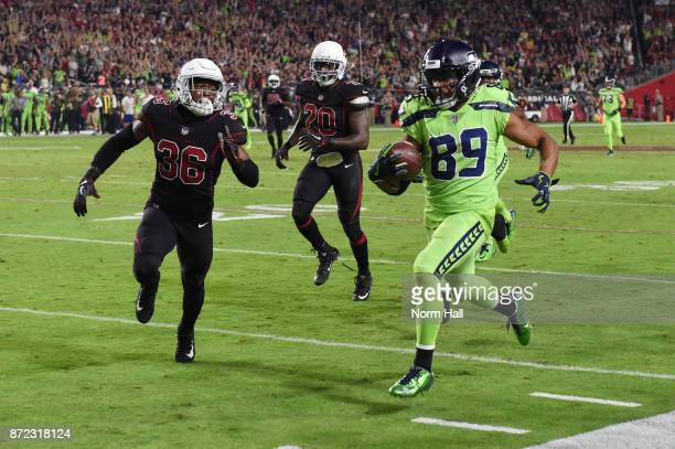 Wide receiver Doug Baldwin of the Seattle Seahawks runs with the football in front of safety Budda Baker and inside linebacker Deone Bucannon of the...