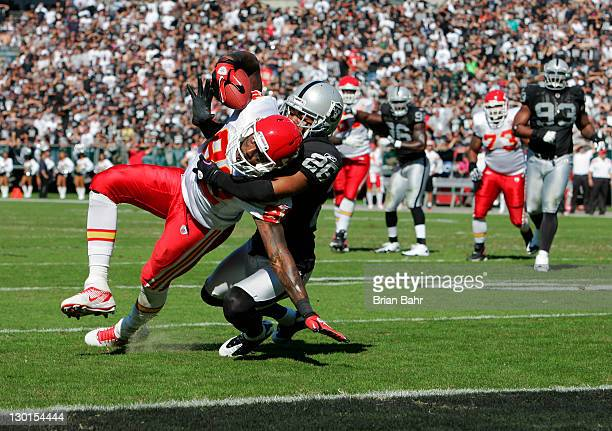 Wide receiver Dwayne Bowe of the Kansas City Chiefs gets pulled down at the sixinch mark by cornerback Stanford Routt of the Oakland Raiders in the...
