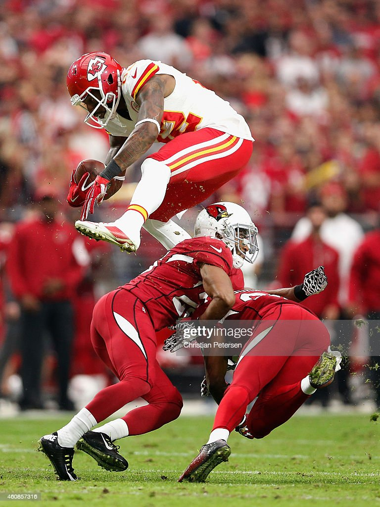 Wide receiver Dwayne Bowe #82 of the Kansas City Chiefs leaps over free safety Rashad Johnson #26 of the Arizona Cardinals (right) and cornerback Justin Bethel #28 (left) during the second quarter of the NFL game at the University of Phoenix Stadium on December 7, 2014 in Glendale, Arizona.