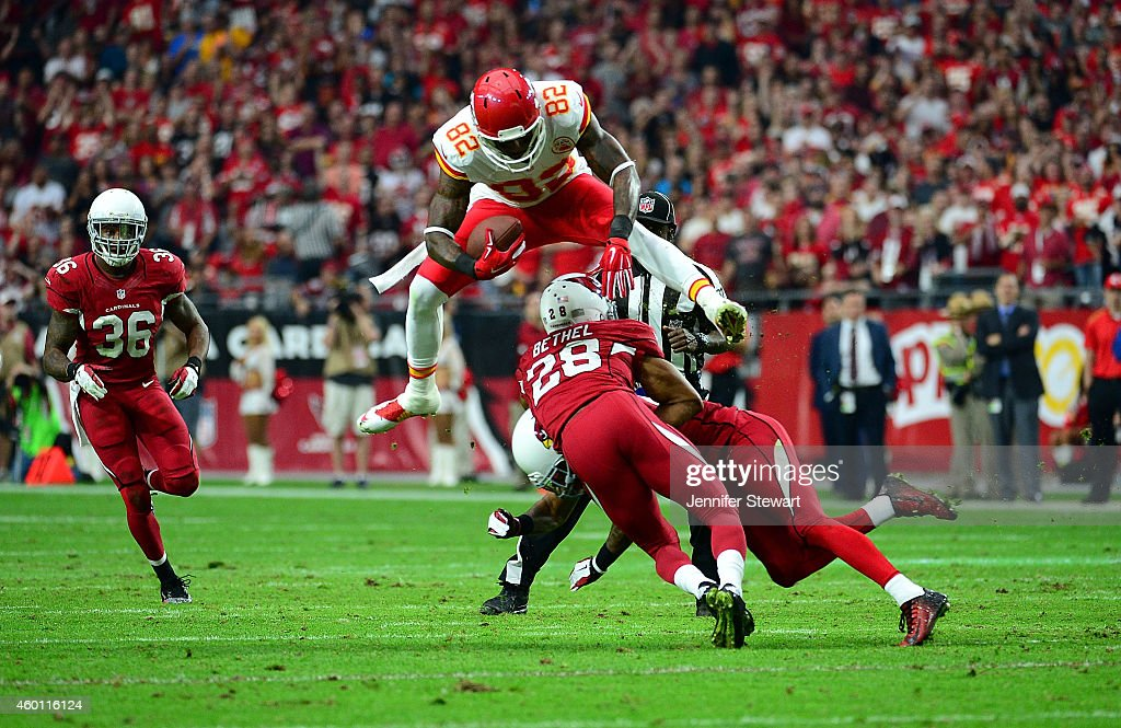 Wide receiver Dwayne Bowe #82 of the Kansas City Chiefs leaps over cornerback Justin Bethel #28 of the Arizona Cardinals (L) and free safety Rashad Johnson #26 (R) in the second quarter during the NFL game at University of Phoenix Stadium on December 7, 2014 in Glendale, Arizona.